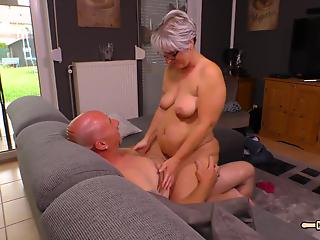 Big-boobed blonde mom gives a passionate blowjob on the couch