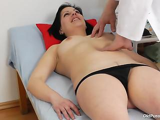 Nasty doctor is playing with a wide-opened pussy of a brunette MILF
