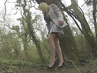 Lusty mature blondie is standing on the knees in the forest and sucking ...